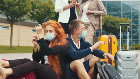 A tourist group in medical masks who are having fun waiting for their flight Live Action