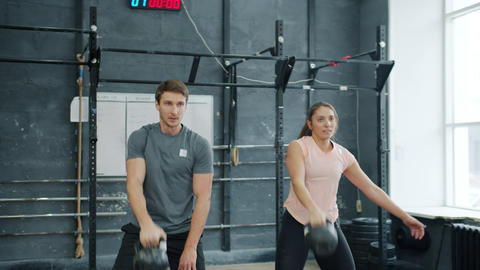 Young couple training in gym weightlifting squatting with kettlebells together Acción en vivo