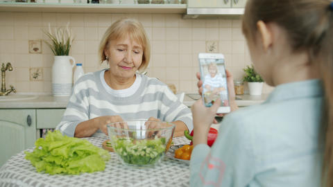 Little girl taking pictures of granny cooking salad then posing for camera with Live Action