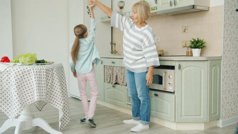 Little girl dancing with grandmother in kitchen, elderly woman showing thumbs-up Live Action