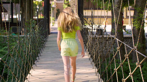 Rear view of girl walking on rope bridge at summertime Live Action