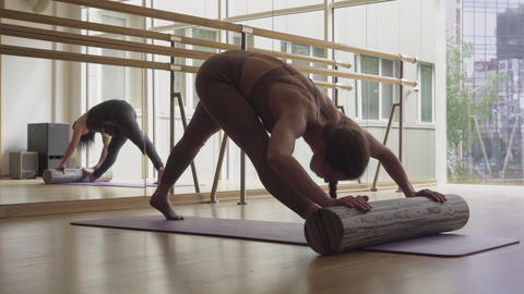 Slim flexible brunette woman stretching on yoga mat using inventory. Wide shot Live Action