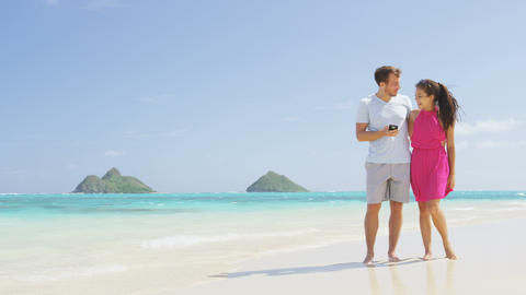 Couple on beach vacation using smart phone app Live Action
