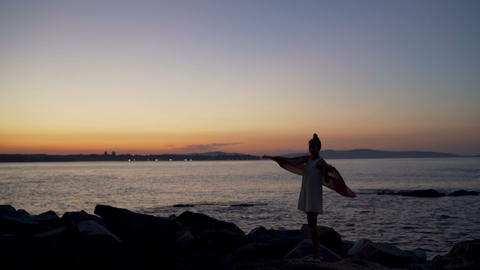 Silhouette of a young woman with scarf on the beach at sunset. Sea surface Live Action
