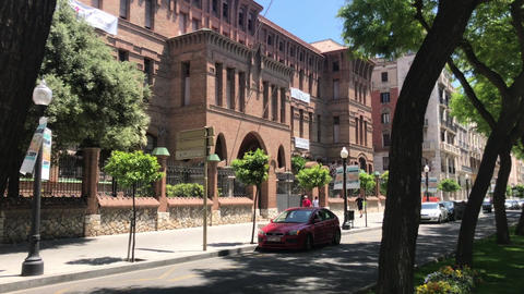 Tarragona, Spain, A street with cars parked on the side of a building Live Action