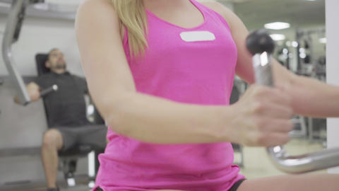 Hands of slim unrecognizable woman pulling equipment in gym. Close-up of Live Action