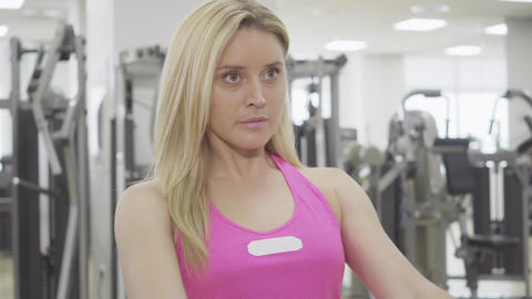 Close-up of blond concentrated sportswoman pulling equipment in gym. Beautiful Live Action
