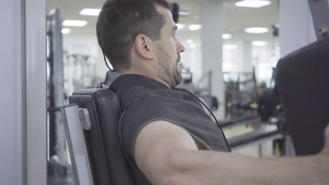 Close-up side view of young concentrated man exercising on gym equipment Live Action