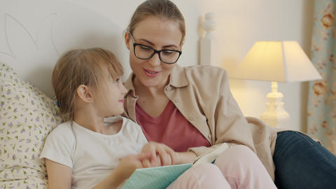 Caring woman and pretty little girl reading book in bed talking discussing Live Action