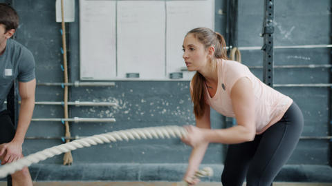 Fit girl training with battle ropes in gym while male trainer assisting Live Action