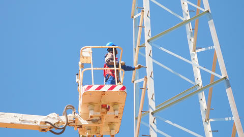worker in helmet checks power transmission tower from basket Acción en vivo