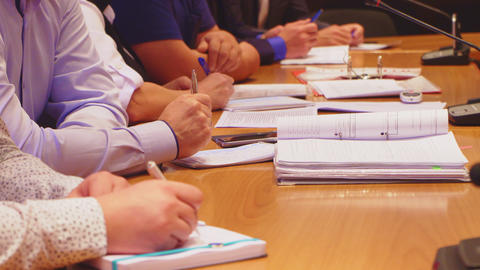 business people with notepads sit at table at daily meeting Live Action