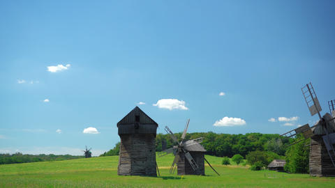 Old windmill and medieval, traditional Ukrainian rural houses on a green meadow. Blue sky with fast Live Action
