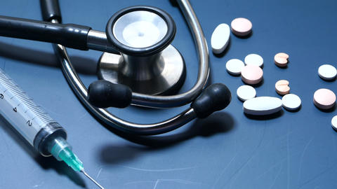 Close up of pills, syringe and stethoscope on color background Live Action