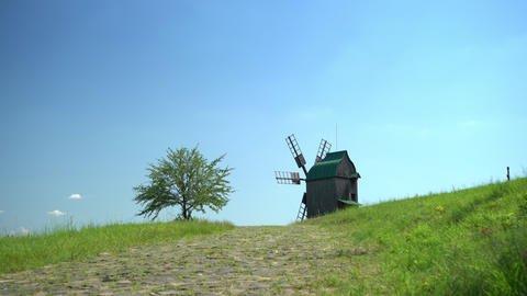Old wodden windmill on a green meadow, field. Lonely green tree in the wind. Blue sky with fast Live Action