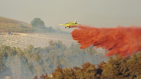 Fire fighter plane drops fire retardant on a forest fire in the hills Live Action