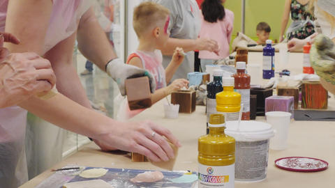 adults with kids take part in painting workshop at store Live Action