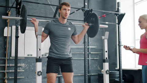Attractive guy student squatting with barbell training indoors with female coach Live Action
