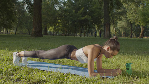 Woman doing planks exercising outdoors in morning Live Action
