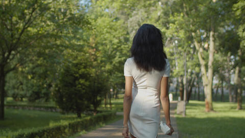 Back view of slim pretty female walking outdoors Live Action