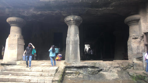 Mumbai, India - November 10, 2019: Elephanta Caves tourists inspect historic Live Action