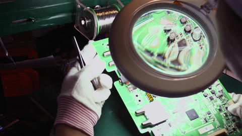Engineer Working with Circuit Board and Magnifying Glass in the Electronic Industry Live Action
