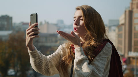 Cute woman holding phone outdoors. Attractive girl looking phone camera Live Action