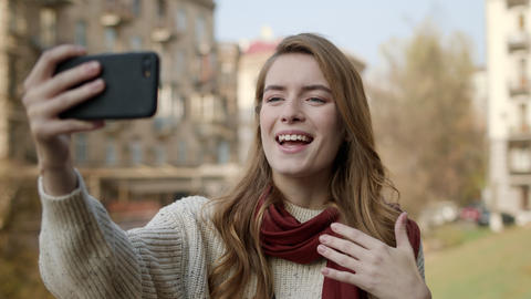 Hipster woman recording selfie video outdoors. Happy girl making video call Live Action