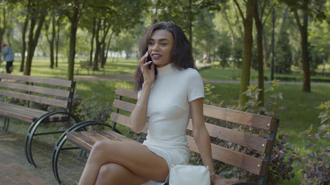 Pretty black woman talking on cellphone on bench Live Action