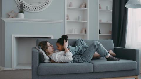 Little joyful daughter girl lying on mother stomach slim harmonic woman on sofa Live Action