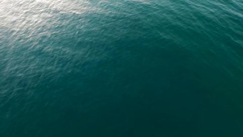 Aerial Over the calm Ocean Water Surface with Blue Sea Ripples And Waves slow Live Action