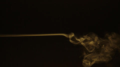 Beautiful gas movement on a black background. Twists of yellow smoke on a black Live Action