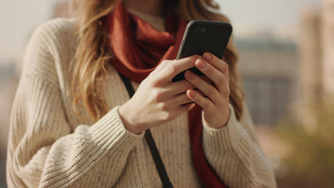 Closeup woman hands using phone outdoors. Unrecognizable girl holding cellphone Live Action