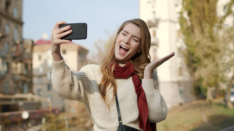 Hipster girl taking selfie outdoors. Flirting woman grimacing for camera Live Action
