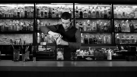 Bartender shaking cocktail in cocktail shaker at bar black and white Live Action