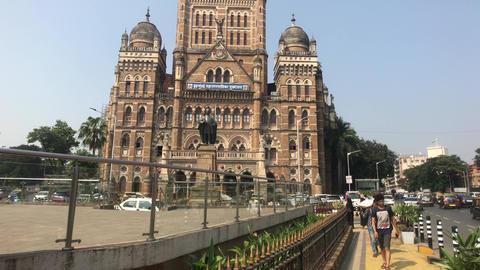 Mumbai, India - November 10, 2019: Chhatrapati Shivaji Terminus tourists walk Live Action
