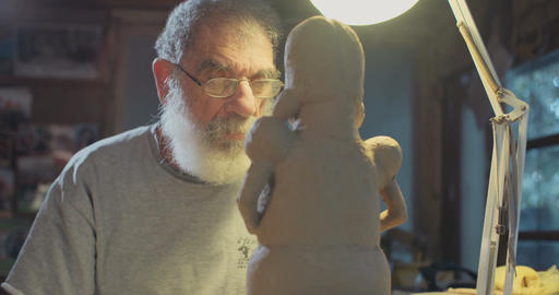 Old artist working in his studio modeling clay sculptures Footage