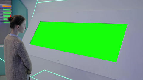 Green screen concept - woman looking at wide green display kiosk at exhibition Live Action