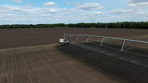 Amazing modern sprinkling machine is watering the seedlings in the field, 4k Live Action