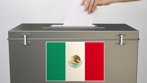Hand putting paper ballot into ballot box with flag of Mexico. Election related Photo