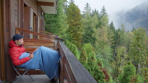Millennial read book on balcony of mountain hotel Acción en vivo