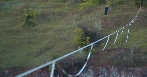 Slackline stretched over a huge natural pit, a man in the background, 4k Acción en vivo