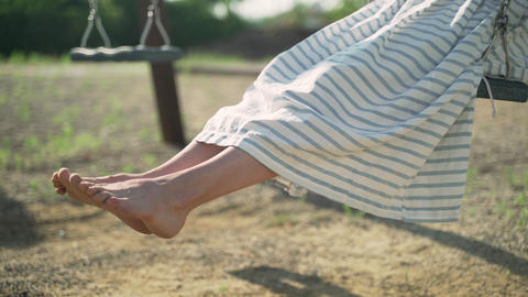 Barefoot girl in a striped dress and a straw hat is swinging on a swing. Chill Acción en vivo