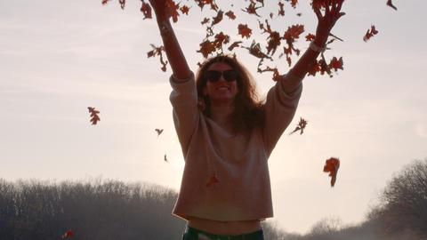 Girl tossing colorful autumn foliage up in air in park Acción en vivo