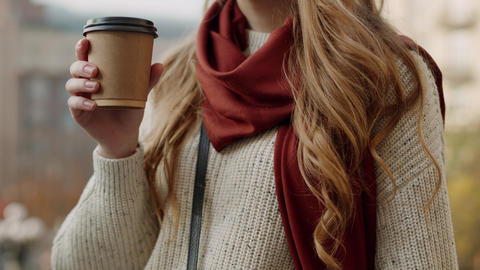 Beautiful girl having coffee outdoors. Hipster woman sipping tea on street Live Action