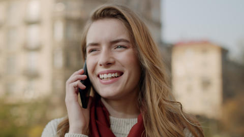 Happy woman calling mobile phone outdoors. Smiling girl talking cellphone Live Action