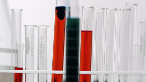 Slow pan of test tubes with red liquid Live Action