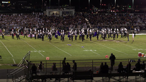 Aerial pan of high school high school band playing Live Action