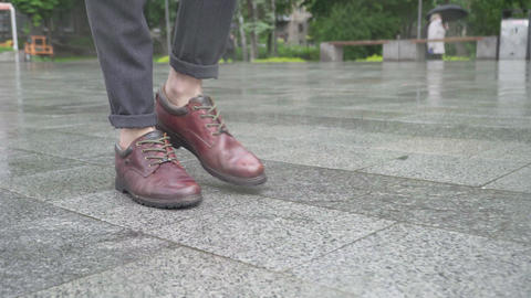 Feet of Caucasian man in elegant shoes walking on wet pavement along city street Live Action