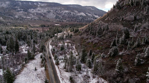 Aerial view of snowy landscape following vehicle driving on road Live Action